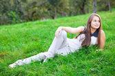 Bela jovem deitado na grama verde — Foto Stock