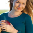Stock Photo: Portrait of a beautiful young woman with apple outdoor