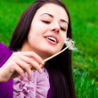 Portrait of a beautiful young woman with dandelion — Stock Photo