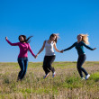 Three young beautiful woman jumping into the field against the s — Stock Photo