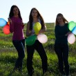 Three young beautiful woman with balloons into the field against — Stock Photo