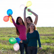 Three young beautiful woman with balloons into the field against — Stock Photo #6158853