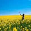 Man with pinwheel standing in a field of yellow rape against the — Stock Photo