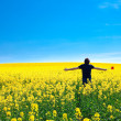 Man with pinwheel standing in a field of yellow rape against the — Stock Photo #6159732