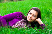 Beautiful young woman lying on green grass — Stock Photo
