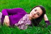 Beautiful young woman lying on green grass — Stock Photo
