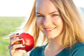 Portrait of a beautiful young woman with apple outdoor — Stockfoto