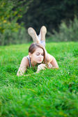 Beautiful young woman lying on green grass — Stockfoto