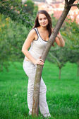 Beautiful young woman standing on green grass — Stock fotografie