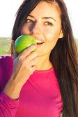 Retrato de una bella mujer joven con manzana al aire libre — Foto de Stock
