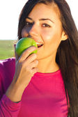 Portrait of a beautiful young woman with apple outdoor — Stock Photo