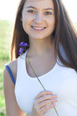 Portrait of a beautiful young woman with flower outdoor — Stock Photo