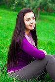 Beautiful young woman sitting on green grass — Stock Photo