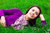 Mooie jonge vrouw liggend op groen gras — Stockfoto