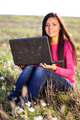 Young beautiful woman with a laptop sitting in the field on sky — Stock Photo