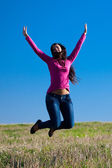 Young beautiful woman jumping into the field against the sky — Stock Photo