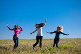 три молодая красивая женщина, прыгнув в поле против s — Стоковое фото