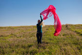 Young beautiful woman jumping with tissue into the field against — Stock Photo