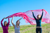 Three young beautiful woman jumping with tissue into the field a — Stock Photo