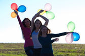 Three young beautiful woman with balloons into the field against — Stock fotografie