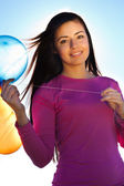 Jonge mooie vrouw met ballonnen in het gebied tegen de s — Stockfoto