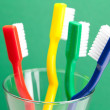 Stock Photo: Colored toothbrush in glass on green background