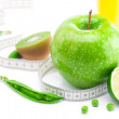 Juice,apple,lime,peas,kiwi and measure tape isolated on white - Stock Photo