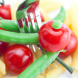 Royalty-Free Stock Photo: Tomatoes, peas, pasta and fork on a plate isolated on white