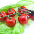 Tomato and lettuce with a fork on a plate isolated on white - Stock Photo
