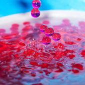 Dekorative perlen in einem spray des wassers auf blauem hintergrund — Stockfoto