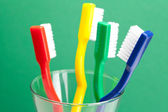 Colored toothbrush in a glass on a green background — Stock Photo