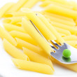 Peas, pasta and fork on a plate isolated on white - Stock Photo