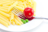 Tomatoes, peas, pasta and fork on a plate isolated on white — Stock Photo