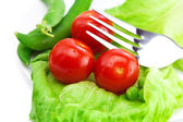 Tomato,peas and lettuce with a fork on a plate isolated on white — Stock Photo
