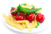 Tomatoes, peas, pasta on a plate isolated on white — Stock Photo