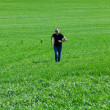 Young man in sunglasses running in green field — Stock Photo #6180229