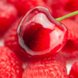 Stock Photo: Cherry on background of raspberry