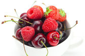 Raspberries, strawberries and cherries in a bowl isolated on whi — Stock Photo