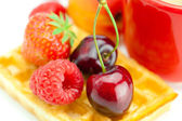 Cappuccino cup, waffles, cherries, strawberries and raspberries — Stock Photo