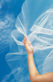 Wedding dress and veil with a hand against the blue sky — Stock Photo