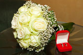 Bridal bouquet and a box with the rings on a glass table — Stock Photo