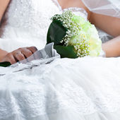 Bouquet in the hands of the bride against the background of dres — Stock Photo