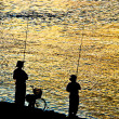 Fisherman silhouette  on shoreline — Stock Photo