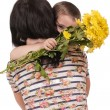 Stock Photo: Mother and son hugging with flowers