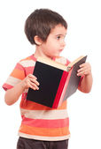 Little boy looks aside while reading book — Stock Photo