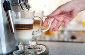 Glasses fileed with capuccino in cofee machine with womans hand — Stock Photo