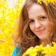 Portrait of redhead woman in yellow bloom — Stock Photo