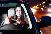 Young woman driving car in the night city — Stock Photo