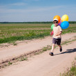 Little boy with colorful balloons running by the country road — Stock Photo