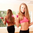 Young wommaking exercise in gym with dumbbell — Stock Photo #6014965